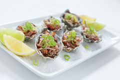 Oysters Kilpatrick. Oven baked oysters kilpatrick on a bed of rocksalt with lemon and lime Royalty Free Stock Photos