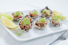 Oysters Kilpatrick with fork. Oven baked oysters kilpatrick on a bed of rocksalt with lemon and lime Stock Photography