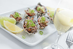 Oysters Kilpatrick with wine. Oven baked oysters kilpatrick on a bed of rocksalt with lemon and lime and a glass of wine Royalty Free Stock Photos