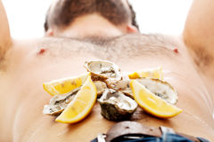 Oysters on man's belly. Royalty Free Stock Photo