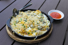 Oysters omelet on the hot pan with chili source Royalty Free Stock Photo