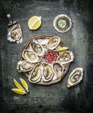Oysters plate with lemon and various sauces  on rustic background Royalty Free Stock Photos
