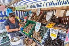 Oysters for sale in Cancale. A local woman sells fresh oysters out of crates at the french coast of Brittany Bretagne in Cancale, France, on August 1, 2014 Stock Photography