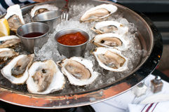 Oysters served raw with sauces. And lemon Royalty Free Stock Photos