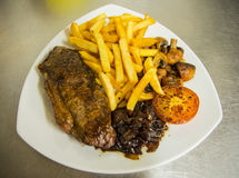 10 oz sirloin steak. Sirloin steak with chips,grilled tomato and mushroom and caramel onion stock image