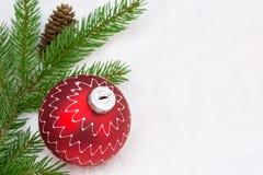 Ozdobni czerwoni boże narodzenia balowi z jedlinową gałąź na śnieżnym backgroun Zdjęcie Royalty Free