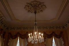Ozdobny krystaliczny świecznik w pięknym pokoju z ekstrawaganckimi zasłonami i tynk bagietami, miękka część barwi obrazy stock