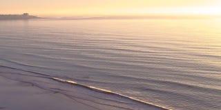 Ozean an den Schwarzen setzen mit Sonnenuntergang im Horizont auf den Strand lizenzfreies stockfoto