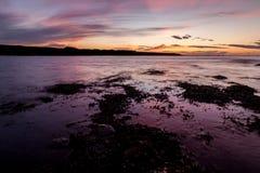 Ozean gegen purpurroten Himmel Stockfotografie