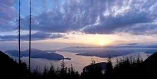 Ozean, Inseln, Wolken und Baum-Schattenbilder bei Sonnenaufgang Stockfotos