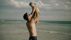Am Ozean Vati, der mit Baby im Wasser spielt stock footage