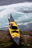 Ozeankajak auf den Strand gesetzt auf felsigem Ufer an den Gezeiten- Rapids Lizenzfreie Stockfotografie