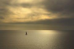Ozeanseesonnenuntergangansicht und schwarzes Segelboot Treibnetz für Thunfischfischen Es Stockfotos