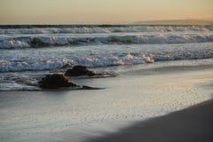 Ozeanufer mit zwei Felsen und Wellen Stockbild