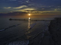 Ozeanufer-Pier bei Sonnenuntergang Stockfotos