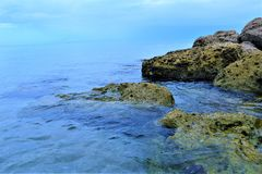 Ozeanwasser kommt in den Strandfelsen an und gibt ein klares Bild der sandigen Unterseite unten Stockbild