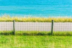Ozeanwasserlandschaft mit Graszaun und -straße Stockbild