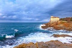 Ozeanwelle und boccale ziehen sich Markstein auf Klippenfelsen zurück. Toskana, Italien. Stockfoto
