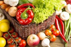 Łozinowy kosz z owoc i warzywo na drewnianym stole Obrazy Stock
