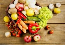Łozinowy kosz z owoc i warzywo na drewnianym stole Obraz Stock