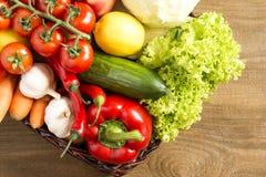 Łozinowy kosz z owoc i warzywo na drewnianym stole Obraz Royalty Free