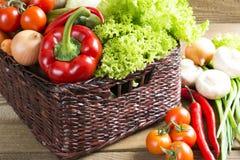 Łozinowy kosz z owoc i warzywo na stole Obrazy Royalty Free