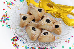 Ozney haman and golden mask symbols of the Jewish holiday of Pur. Hamantachen, traditional pastry on decorative plate and a mask for the Jewish holiday of Purim stock photography