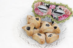 Ozney haman and masquerade mask symbols of the Jewish holiday of. Hamantachen, traditional pastry on decorative plate and a mask for the Jewish holiday of Purim royalty free stock images