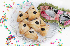 Ozney haman and masquerade mask symbols of the Jewish holiday of. Hamantachen, traditional pastry on decorative plate and a mask for the Jewish holiday of Purim royalty free stock photos