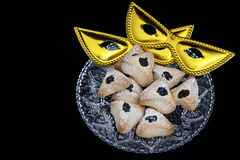 Ozney haman pastry and masquerade mask symbols of the Jewish hol. Hamantachen, traditional pastry on decorative plate and a mask for the Jewish holiday of Purim royalty free stock image