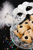 Ozney haman and white masquerade mask symbols of the Jewish holi. Hamantachen, traditional pastry on decorative plate and a mask for the Jewish holiday of Purim stock photos