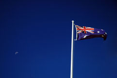 Ozzie flag. Waving australian flag on a post, blue sky, moon Stock Images