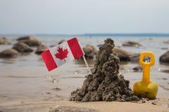 Pá, castelo da lama e bandeira de Canadá Fotografia de Stock Royalty Free