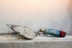 Pá de pedreiro na parede do cimento fotos de stock
