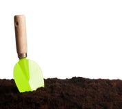 Pá de pedreiro verde na terra Imagens de Stock Royalty Free