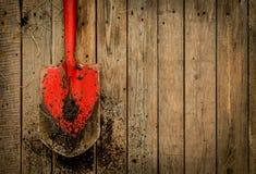 Pá vermelha suja (ferramenta de jardinagem) no fundo de madeira rústico Foto de Stock