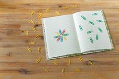Página abierta del cuaderno, clips coloreados Fondo de madera Visión superior Fotos de archivo