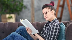 Página de papel de torneado confiada del libro de lectura de la mujer del adolescente que disfruta de fin de semana en casa metrajes