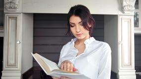 Página de torneado concentrada del papel del libro de lectura de la chica joven que disfruta de fin de semana en casa metrajes