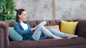 Página de torneado hermosa joven pensativa del libro de lectura de la mujer que se sienta en tiro lleno del sofá en casa almacen de metraje de vídeo