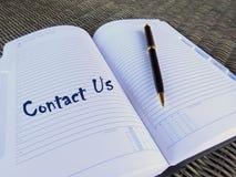 Página del orden del día con el contacto nosotros Foto de archivo