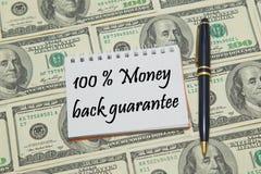 Página do caderno com GARANTIA 100% TRASEIRA do DINHEIRO do texto no fundo do dólar Fotos de Stock
