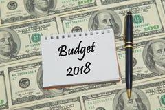 A página do caderno com palavras INCLUI NO ORÇAMENTO 2018 no fundo do dólar Imagem de Stock