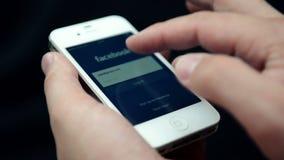 Página do início de uma sessão de Facebook em uma exposição branca do iPhone vídeos de arquivo