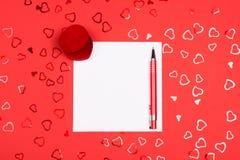 Página en blanco con la pluma en fondo rojo con confeti en forma de corazón fotos de archivo