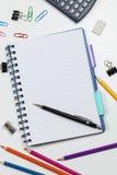 Página en blanco del cuaderno de notas en un escritorio blanco ocupado Imagen de archivo libre de regalías