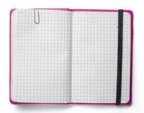 Página en blanco del cuaderno rosado con el clip de papel y la correa elástico i Foto de archivo
