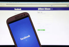 Página web de Facebook en smartphone y el ordenador portátil Foto de archivo