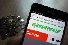 Página web de Greenpeace exhibida en el smartphone de Samsung y la pila de monedas foto de archivo