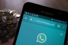 Página web de WhatsApp exhibida en el smartphone de Samsung y la pila de monedas foto de archivo